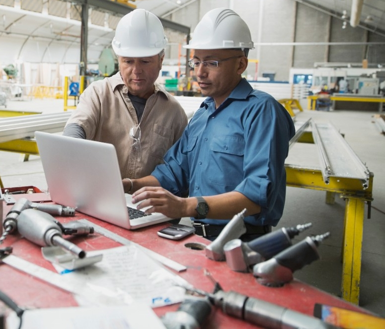 stock-photo-workers-at-laptop-in-manufacturing-plant-85464847