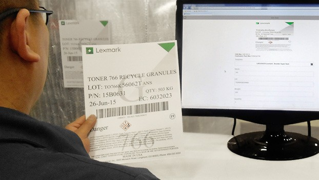 Lexmark employee sitting at computer holding old manufacturing hazardous label in order to make a new one on the computer screen.