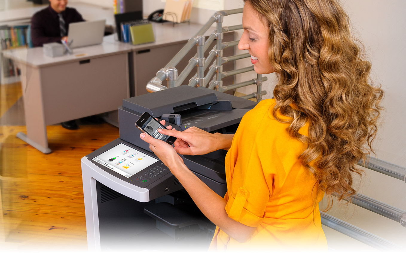 lady with mobile in front of a printer